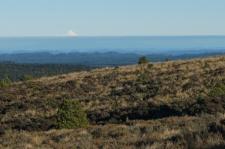 Tālumā pie horizonta Taranaki vulkāns.