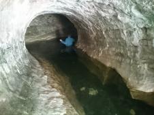 Cave Stream ieeja. Ar džemperi mugurā un cepuri galvā peldam iekšā nezināmajā.