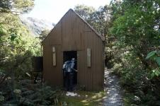 Tieši takas malā kartē neatzīmēta kalnu būdiņa ar pabriesmīgu bardaku iekšpusē. Laikam privātais hut (ar tādiem pilna Jaunzēlande), tik durvis vaļā palikušas.
